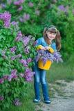 Muchacha hermosa adorable linda de la mujer de la señora con el pelo moreno en un prado del arbusto de la púrpura de la lila Gent Fotografía de archivo