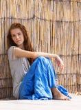Muchacha hermosa al lado de la pared de bambú Foto de archivo