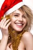 Muchacha hermosa alegre alegre en imagen del ` s del Año Nuevo con maquillaje festivo, Santa Claus que lleva cara de la belleza d Imágenes de archivo libres de regalías