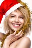 Muchacha hermosa alegre alegre en imagen del ` s del Año Nuevo con maquillaje festivo, Santa Claus que lleva cara de la belleza d Fotos de archivo