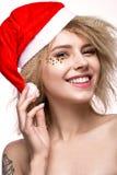 Muchacha hermosa alegre alegre en imagen del ` s del Año Nuevo con maquillaje festivo, Santa Claus que lleva cara de la belleza d Foto de archivo