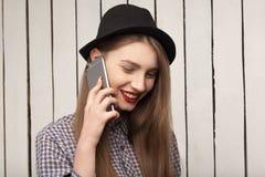 Muchacha hermosa, alegre, alegre, feliz en camisa y sombrero que hablan en el teléfono Imagenes de archivo