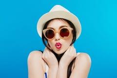 Muchacha hermosa alegre en vidrios del sombrero y de sol Sonriendo extensamente, mirando y señalando a un lado Equipo del verano  Imagen de archivo