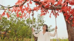 Muchacha hermosa asiática de Vietnam con el pelo largo en un oscilación en el jardín del otoño metrajes