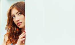 Muchacha hermosa atractiva con el pelo rojo y los labios llenos que mira furtivamente de detrás la pared blanca Imagen de archivo