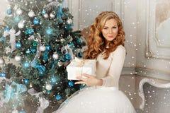 Muchacha hermosa atractiva con el pelo rubio grueso lujoso en un t blanco Imagenes de archivo
