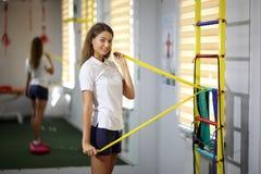 Muchacha hermosa, atractiva en el gimnasio Contratan a una chica joven hermosa a aptitud con un ampliador Foto de archivo