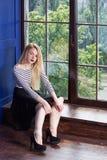 Muchacha hermosa cerca de las ventanas en casa Foto de archivo libre de regalías