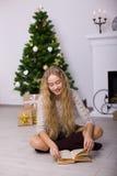 Muchacha hermosa cerca de un árbol de navidad en el cuarto Fotografía de archivo libre de regalías