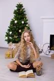 Muchacha hermosa cerca de un árbol de navidad en el cuarto Fotos de archivo libres de regalías