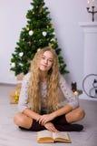 Muchacha hermosa cerca de un árbol de navidad en el cuarto Fotos de archivo