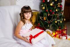 Muchacha hermosa cerca del árbol de navidad adornado, controles un blanco fotografía de archivo