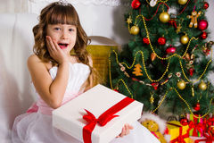 Muchacha hermosa cerca del árbol de navidad adornado, controles un blanco fotos de archivo