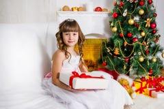 Muchacha hermosa cerca del árbol de navidad adornado, controles un blanco foto de archivo libre de regalías