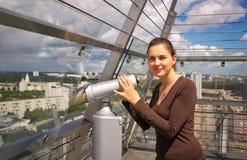 Muchacha hermosa cerca del telescopio en el tejado del edificio Fotos de archivo libres de regalías