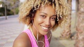 Muchacha hermosa con corte de pelo afro en la playa almacen de video