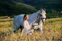 Muchacha hermosa con el caballo blanco en campo Fotos de archivo libres de regalías