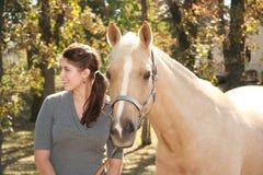 Muchacha hermosa con el caballo del Palomino Imagen de archivo libre de regalías