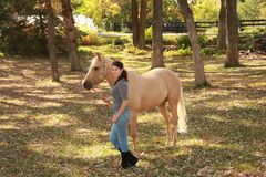 Muchacha hermosa con el caballo del Palomino Fotografía de archivo libre de regalías