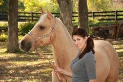 Muchacha hermosa con el caballo del Palomino Fotografía de archivo