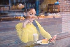 Muchacha hermosa con el café visto a través de la ventana Foto de archivo libre de regalías