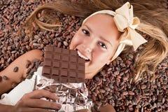 Muchacha hermosa con el chocolate en granos de cacao Foto de archivo