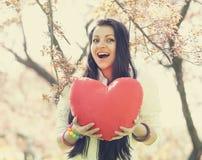 Muchacha hermosa con el corazón del juguete en parque de la primavera Foto de archivo