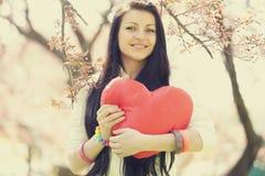 Muchacha hermosa con el corazón del juguete en parque de la primavera Imagen de archivo