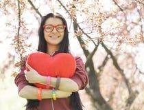 Muchacha hermosa con el corazón del juguete en parque de la primavera Fotografía de archivo libre de regalías