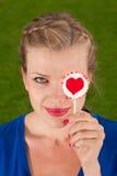 Muchacha hermosa con el corazón del lollipop en su mano Foto de archivo