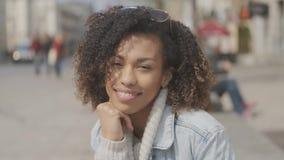 Muchacha hermosa con el corte de pelo afro que se sienta en banco en la calle de la ciudad almacen de metraje de vídeo