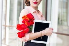 Muchacha hermosa con el dispositivo electrónico y las flores Imagen de archivo