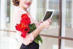 Muchacha hermosa con el dispositivo electrónico y las flores rojas Foto de archivo libre de regalías