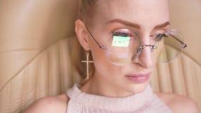 Muchacha hermosa con el funcionamiento de vidrios en un ordenador portátil metrajes