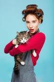 Muchacha hermosa con el gato bonito en las manos que presentan y que miran a la cámara Imagen de archivo