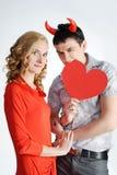 Muchacha hermosa con el hombre joven con los claxones rojos fotografía de archivo