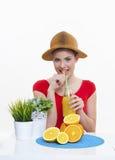 Muchacha hermosa con el jugo de limón anaranjado de la fruta fresca Fotografía de archivo libre de regalías