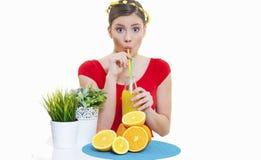 Muchacha hermosa con el jugo de limón anaranjado de la fruta fresca Fotos de archivo