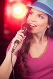 Muchacha hermosa con el micrófono que se coloca en barra Imagenes de archivo