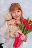 Muchacha hermosa con el oso y los tulipanes de peluche Imagen de archivo libre de regalías