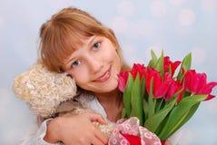 Muchacha hermosa con el oso y los tulipanes de peluche Imagenes de archivo