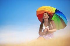Muchacha hermosa con el paraguas colorido que se relaja en el campo Foto de archivo libre de regalías