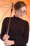 Muchacha hermosa con el paraguas y los vidrios anaranjados Imágenes de archivo libres de regalías