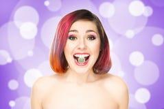Muchacha hermosa con el pelo coloreado con un caramelo de la jalea Fotografía de archivo libre de regalías