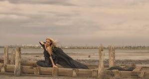 Muchacha hermosa con el pelo del vuelo en vestido en la naturaleza imagenes de archivo