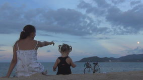 Muchacha hermosa con el pelo largo con un bebé que se sienta con el suyo de nuevo a la cámara en la playa arenosa miran el cielo  metrajes
