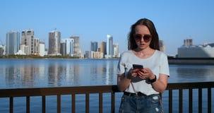 Muchacha hermosa con el pelo largo en gafas de sol usando el app del smartphone en el muelle del r?o de la puesta del sol cerca d almacen de video