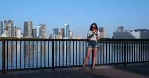 Muchacha hermosa con el pelo largo en gafas de sol usando el app del smartphone en el muelle del r?o de la puesta del sol cerca d metrajes