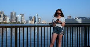 Muchacha hermosa con el pelo largo en gafas de sol usando el app del smartphone en el muelle del r?o de la puesta del sol cerca d almacen de metraje de vídeo