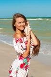 Muchacha hermosa con el pelo largo en la playa con el SE Foto de archivo